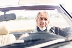 驾驶一辆敞篷车经典汽车的老人 库存照片