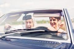驾驶一辆敞篷车经典汽车的资深夫妇 免版税图库摄影