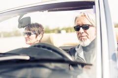 驾驶一辆敞篷车经典汽车的资深夫妇 免版税库存照片
