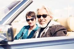 驾驶一辆敞篷车经典汽车的资深夫妇 库存图片