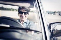 驾驶一辆敞篷车经典汽车的资深妇女 免版税库存照片