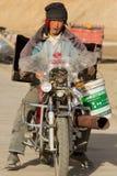 驾驶一辆残破的地方中国摩托车的西藏工作者在西藏 免版税库存照片
