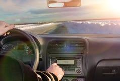 驾驶一辆汽车的一个人在冬天 免版税库存图片
