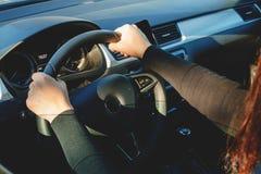 驾驶一辆汽车的一个少妇在一个晴天 免版税库存照片