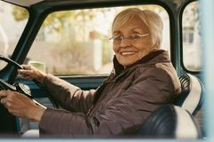 驾驶一辆汽车的资深妇女在冬日 免版税库存图片