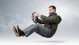 驾驶一辆汽车的滑稽的人在冬天 库存照片