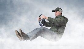驾驶一辆汽车的滑稽的人在冬天 库存图片