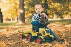 驾驶一辆玩具卡车的小孩在公园 库存图片
