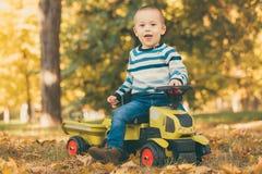 驾驶一辆玩具卡车的男孩在公园户外 免版税库存图片