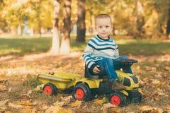 驾驶一辆玩具卡车的男孩在公园 免版税库存照片