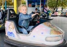 驾驶一辆碰撞用汽车的一个小男孩 库存图片
