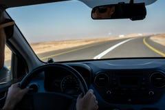 驾驶一辆租用的汽车的年轻人在沙漠 免版税库存照片