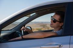 驾驶一辆租用的汽车的愉快的年轻人在以色列的沙漠 图库摄影