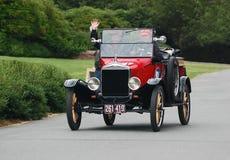 驾驶一辆红色模型T敞篷车的夫妇 免版税库存图片