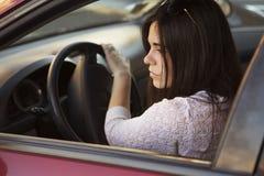 驾驶一辆红色汽车的年轻美丽的深色的白种人妇女 总和 免版税库存照片