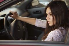 驾驶一辆红色汽车的年轻美丽的深色的白种人妇女 总和 图库摄影