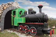 驾驶一辆老蒸汽机车的小女孩 免版税库存照片