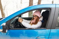 驾驶一辆蓝色汽车的一个桃红色帽子的女孩在冬天 库存图片