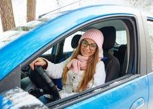 驾驶一辆蓝色汽车的一个桃红色帽子的女孩在冬天 免版税库存图片