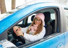 驾驶一辆蓝色汽车的一个桃红色帽子的女孩在冬天 库存照片
