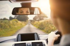 驾驶与她的在镜子的反射的妇女 库存照片