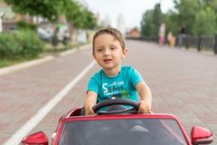 驾驶乘玩具汽车的微笑的小男孩 活跃休闲和体育孩子的 愉快的小孩画象在街道上的 滑稽逗人喜爱 库存图片