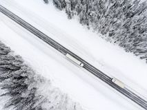 驾驶从相反方向的半拖车卡车和卡车在溜滑冬天涂柏油高速公路,从寄生虫的顶视图 免版税图库摄影