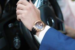 驾驶他的汽车,在方向盘的手的商人 有金黄手表的手 岬概念 库存照片