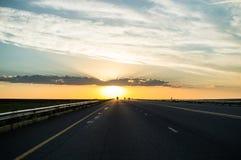 驾驶入在高速公路的日落,自由州,南非 图库摄影