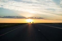 驾驶入在高速公路的日落,自由州,南非 免版税库存照片