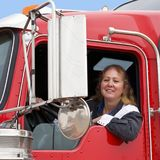 驾驶十八轮车的妇女 免版税库存照片