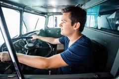 驾驶卡车的消防队员在消防局 免版税库存照片