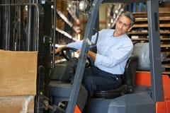 驾驶叉架起货车的人在大商店里 免版税库存图片