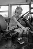 驾驶古色古香的校车的年轻男孩 免版税库存照片