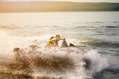 驾驶喷气机滑雪,阻碍和做水的浪花一个人滴下与在背景的阳光 免版税库存照片