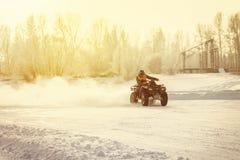 驾驶在一条多雪的高速公路的ATV 免版税图库摄影