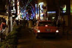 驾驶在一条拥挤步行街道上的计程车,装饰用圣诞灯,在新宿区 免版税库存图片