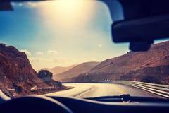 驾驶在一条有风山路的一辆汽车 免版税库存图片