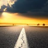 驾驶在一条空的柏油路在日出 免版税库存照片