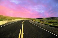 驾驶在一条空的柏油路通过绿色调遣在c 图库摄影