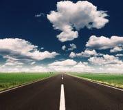 驾驶在一条空的高速公路美好的晴天 免版税图库摄影