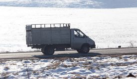 驾驶在一条路的卡车在冬天 免版税库存图片
