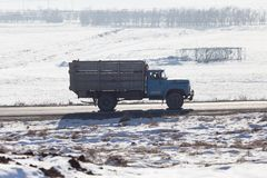 驾驶在一条路的卡车在冬天 免版税库存照片