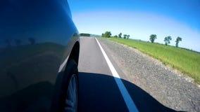驾驶在一条高速公路的一辆汽车沿绿色象草的领域在一个晴朗的夏日 照相机在汽车的边登上了 股票视频