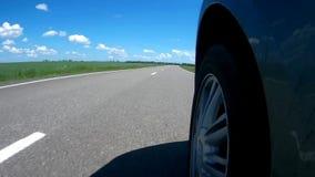驾驶在一条高速公路的一辆汽车沿绿色象草的领域在一个晴朗的夏日 照相机在汽车的边登上了 影视素材