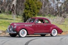1940年驾驶在乡下公路的别克特别小轿车 免版税库存照片