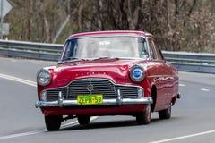 1959年驾驶在乡下公路的福特过眼云烟的轿车 免版税库存图片