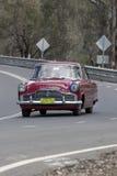 1959年驾驶在乡下公路的福特过眼云烟的轿车 库存照片