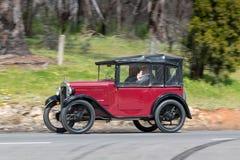 驾驶在乡下公路的葡萄酒1930年奥斯汀7亲密的游览车 免版税图库摄影