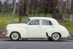 1955年驾驶在乡下公路的霍尔顿FJ轿车 库存照片